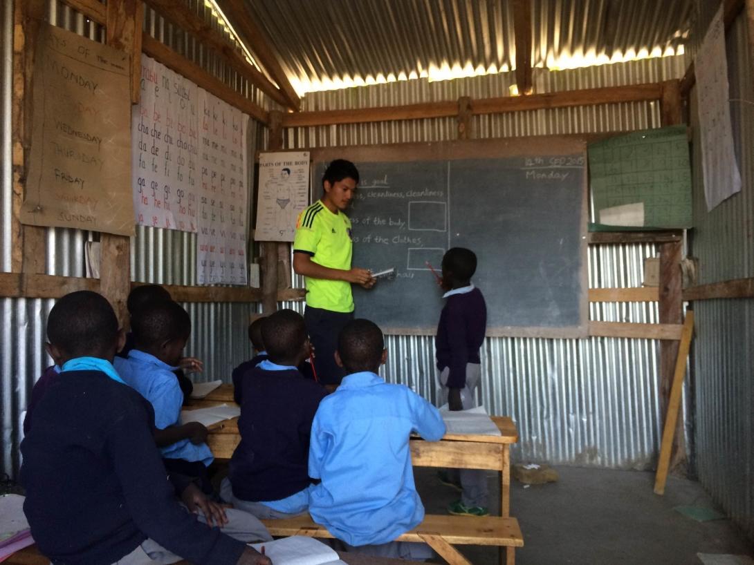 En lärarvolontär stöttar lokala lärare genom att undervisa elever i grupper, under hans volontärresa utomlands.